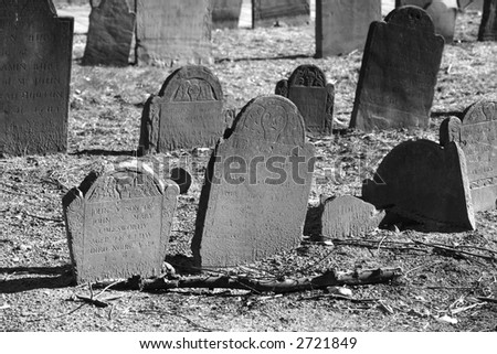 ancient grave stones in black and white in bright sun light on a beautiful winter's day - stock photo
