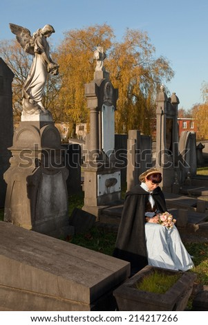 Ancient graveyard and a Victorian widow holding roses - stock photo