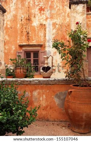 ancient greek courtyard with terracotta flowerpots  - stock photo