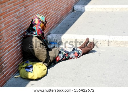ancient Gypsy with lurid clothes while begging on the street - stock photo