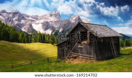 Ancient Hut on a wonderful mountain scenario - The Alps at sunset. - stock photo