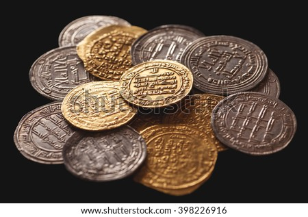 Ancient islamic golden and silver coins isolated on black, selective focus, closeup - stock photo
