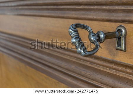Ancient key in the keyhole of antique furniture - stock photo