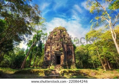 Ancient Khmer pre Angkor architecture. Sambor Prei Kuk temple ruins with giant banyan trees under blue sky. Kampong Thom, Cambodia travel destinations - stock photo