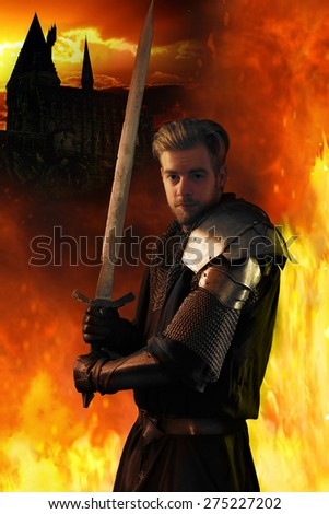 Ancient knight in metal armor with sword on a fiery background - stock photo