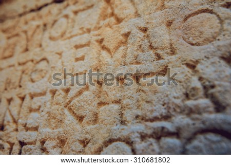 Ancient letters carved on a stone wall. Background - stock photo