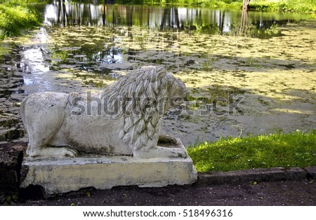 Ancient lion sculpture near old pond in manor park