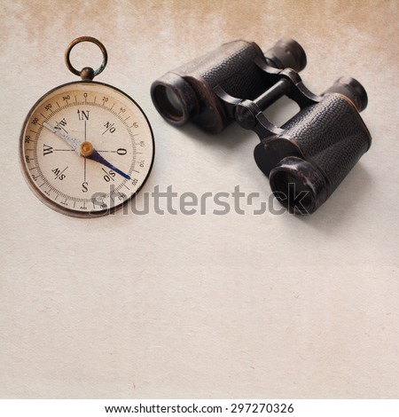 Ancient magnetic exploration compass, aged binocular. Manuscript paper textured background. copy space. closeup - stock photo