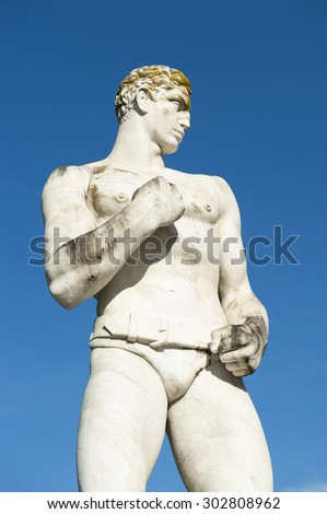 Ancient marble statue of muscular boxer against bright blue sky - stock photo