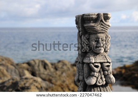 Ancient Maya Statue on the Rocks near the Ocean - stock photo