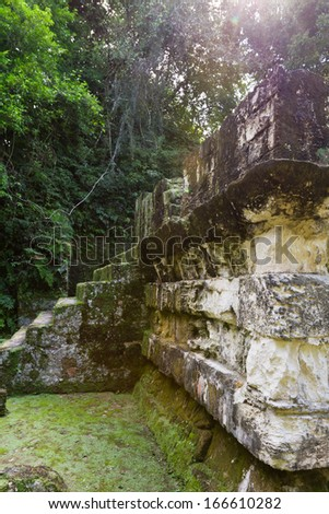 Ancient Mayan ruins in Tikal Guatemala half covered and underground - stock photo