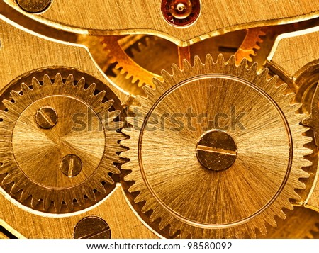 Ancient mechanical gears close up, golden texture - stock photo