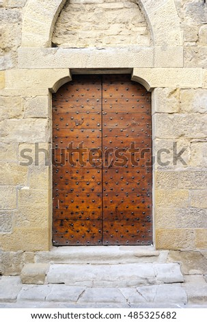 Ancient medieval door of an old palace in the city centre of Pisa (Tuscany, Italy). Color image.