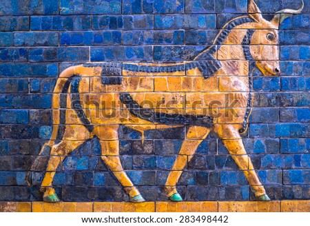 Ancient mosaic on the Ishtar Gate wall with mythical bull, Istanbul museum. Babylonian mosaic, fragment of the Ishtar Gate. - stock photo
