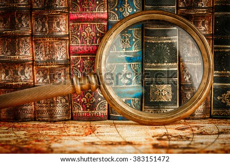 Ancient old books and magnifying glass - stock photo