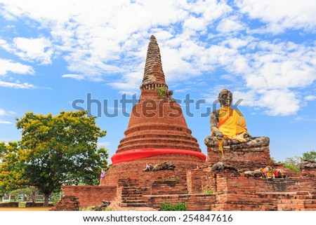 ancient outdoor temple ruined with big buddha and pagoda in blue sky