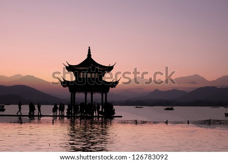 ancient pavilion on the west lake with sunset in hangzhou,China.