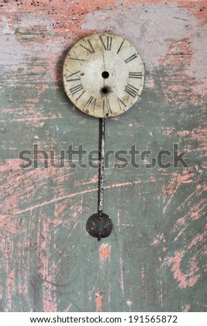 Ancient pendulum clock on a broken wall. - stock photo