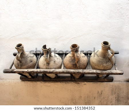 Ancient pitchers on stucco wall - stock photo