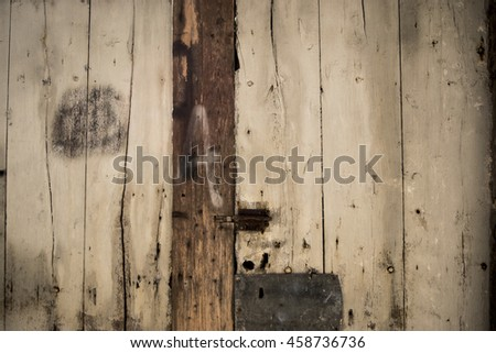 Ancient plank wood door with rusted lock and graffiti of the letter a