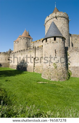 Ancient rampart tower and moat of Carcassonne chateau. The Carcassone is a fortified chateau in Aude France.It was added to the UNESCO list of World Heritage Sites in 1997. - stock photo