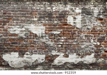 Ancient red brick wall with remaining plaster spots; texture; background