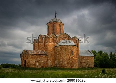 Ancient red stone cathedral view with rain clouds. Novgorod, Russia - stock photo