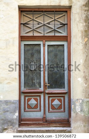 Ancient red wooden door with glass and decoration elements. Tallinn, Estonia