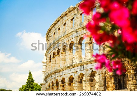 Ancient Roman Amphitheater in Pula, Croatia. Popular Touristic Destination of Istria at Adriatic Sea. Defocused Flowers on the Foreground. Copy Space. - stock photo