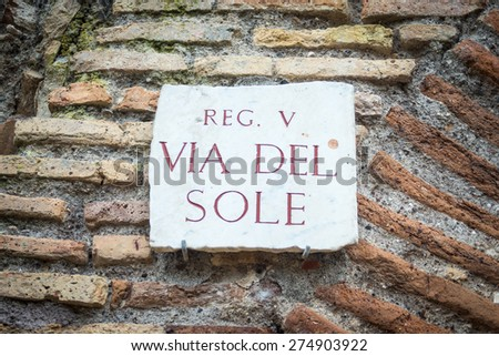 Ancient roman signpost in Ostia old town, Rome, Italy. Broken, weathered and damaged marble roman inscription, placed on brick boundary wall. - stock photo