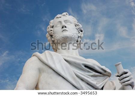 Ancient Roman statue against blue sky - stock photo