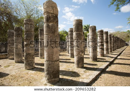 ancient round stone column rows on Mayan archaelogical site - stock photo