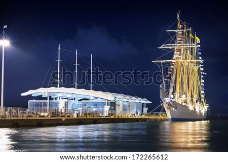 Ancient sailing ship in a modern port - stock photo