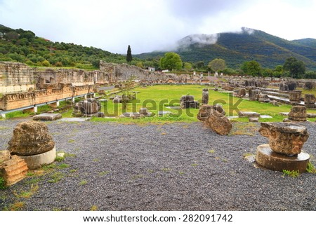 Ancient sanctuary of Messene with fallen columns and blocks of stone on a green meadow, Greece