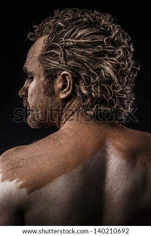 Ancient sexy warrior covered in mud, back - stock photo