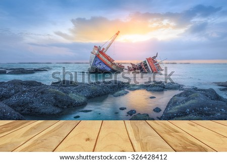 Ancient shipwrecks in the sea with sunset background. - stock photo