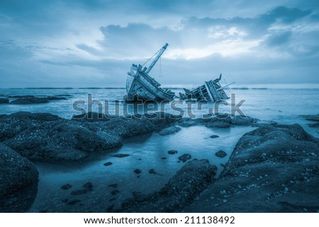 Ancient shipwrecks in the sea with sunset background blue color tone. - stock photo