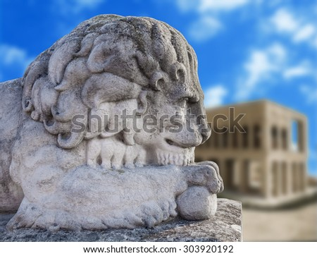 Ancient statue of a lion  isolated on old village background - stock photo