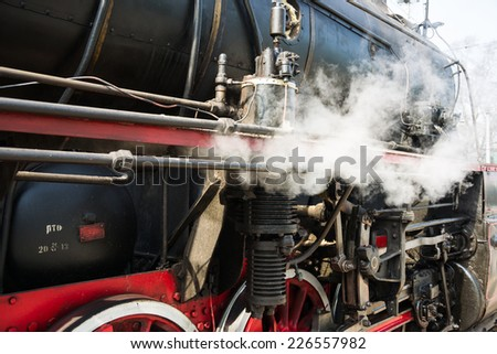 Ancient steam locomotive in steam. Live steam around mechanical parts, wheels and equipment of the train. The foretaste of an interesting travel - stock photo