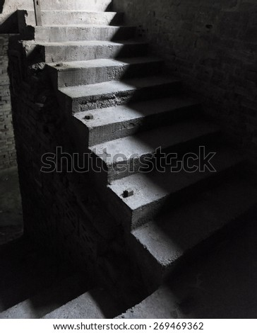 Ancient steep concrete staircase with bright light from above and dark shadows - stock photo