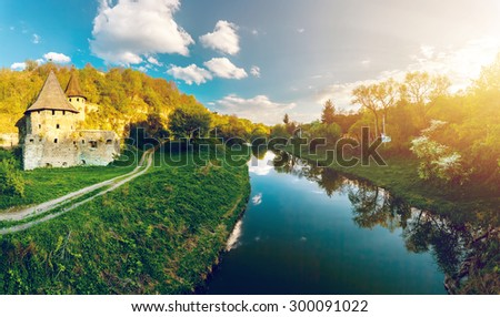 Ancient  stone castle standing near the river. Sunset time - stock photo