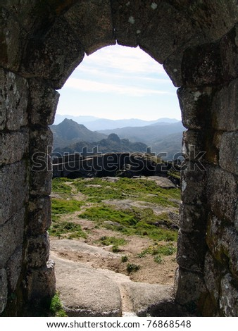 ancient stone door historic with mountains in background - stock photo