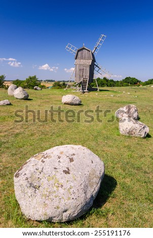 Ancient stone henge in front of traditional windmill - stock photo