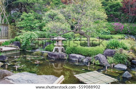 Ancient stone lantern near little pond in Japanese park