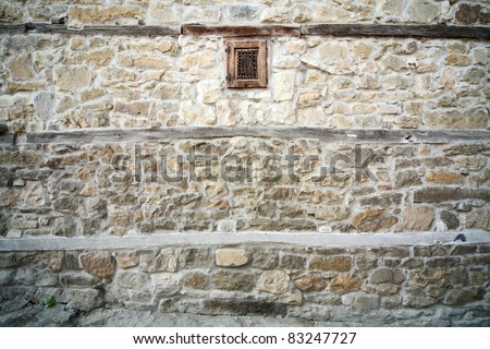 ancient stone wall with wooden small window - stock photo