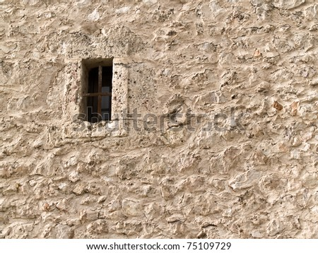Ancient stoned wall with a little window