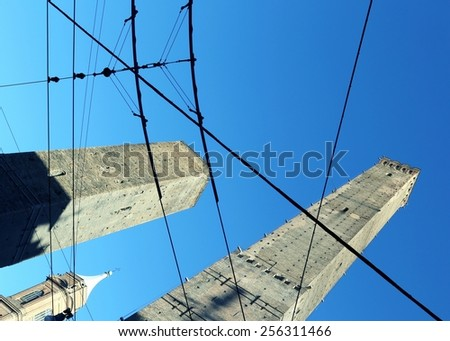 ancient tower called DEGLI ASINELLI in Bologna Center in Italy with tram wires
