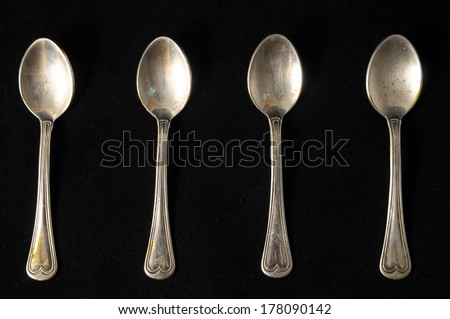 Ancient Vintage Silver Flatware on a Black Background - stock photo