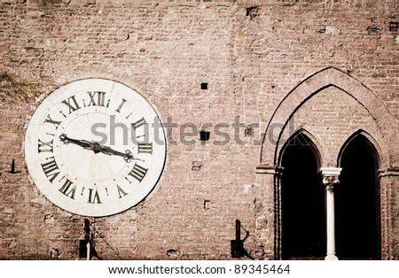 Ancient wall clock on the outside of a medieval palace in Siena, Italy, that used be a hospital and is now a museum. - stock photo