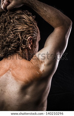 Ancient warrior covered in mud, back - stock photo